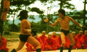 """Bruce waves """"Hi"""" to Sammo Hung before hitting him with a spinning back kick"""